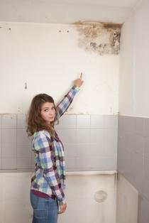 Frau zeigt auf Schimmel in der Küche